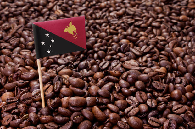 The flag of Papua New Guinea sticking in roasted coffee beans.(series)